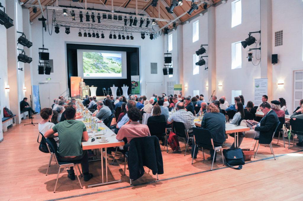 Blick auf die Bühne über den gefüllten Vortragssaal beim Bayerischen Landschaftspflegetag 2018 in Eichstätt.