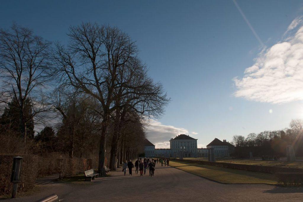 Eine Exkursionsgruppe geht im Schlosspark Nymphenburg beim Natura 2000-Gipfel in München durch den Schlosspark Nymphenburg auf einem Weg zwischen Baumreihe und Beeten. Im Hintergrund das Schloss Nymphenburg.