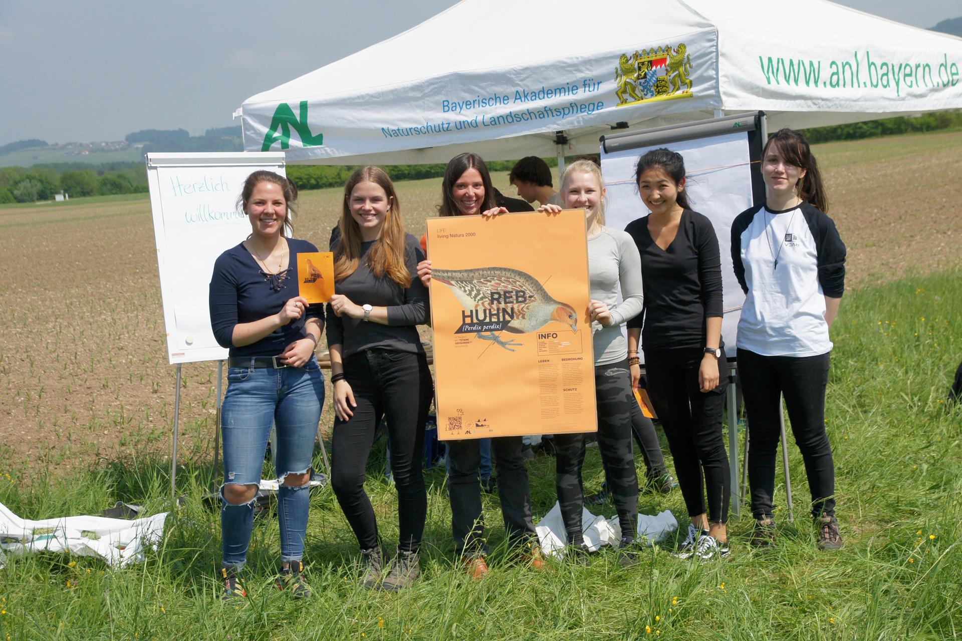 Eine Gruppe junger Schülerinnen stehen am Feld unter einem Pavillon und präsentieren ein Plakat zum Rebhuhn.