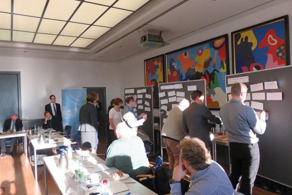Teilnehmer der projektbegleitenden Arbeitsgruppe heften während eines Workshops im Herbst 2017 Moderationskarten an Pinnwände.