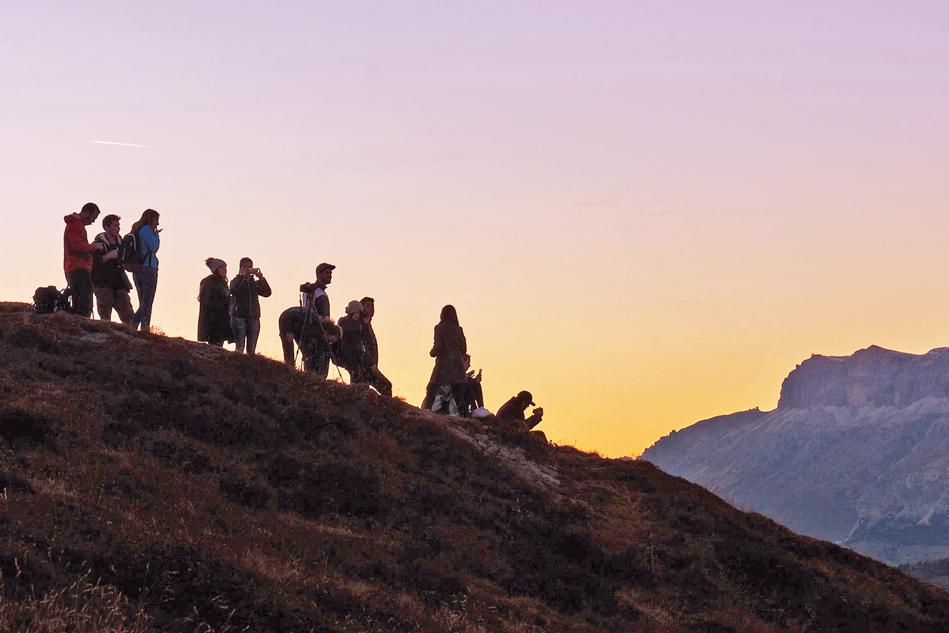 Junge Leute auf einem Hügel. Im Hintergrund ein Sonnenuntergang