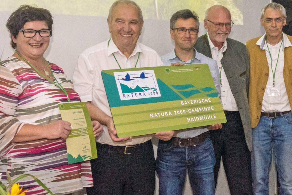 """Eine Frau und vier Männer mittleren Alters schauen lächelnd in die Kamera. Zwei der Männer halten eine grüne Tafel mit der Aufschrift """"Bayerische Natura 2000-Gemeinde Haidmühle""""."""