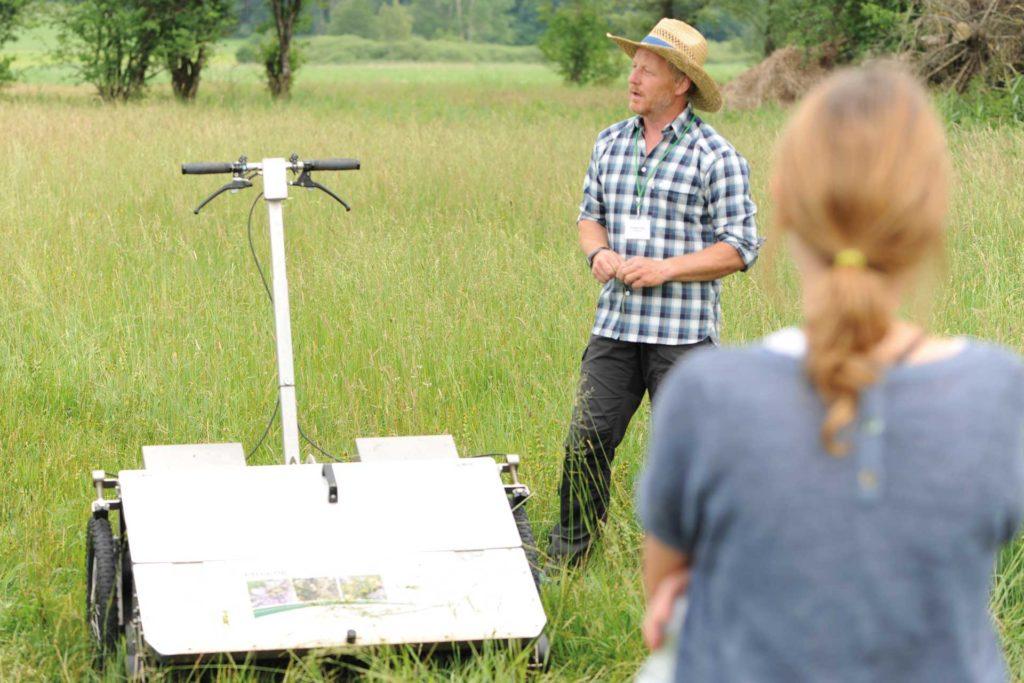 """Landwirt Christian Fendt demonstrierte das elektrisch betriebene Samensammelgerät """"e-beetle"""", das dazu dient, aus artenreichen Wiesenbeständen Saatgut zu gewinnen, indem die Samen der Wiesenpflanzen mit einer rotierenden Bürste """"ausgefegt"""" werden."""