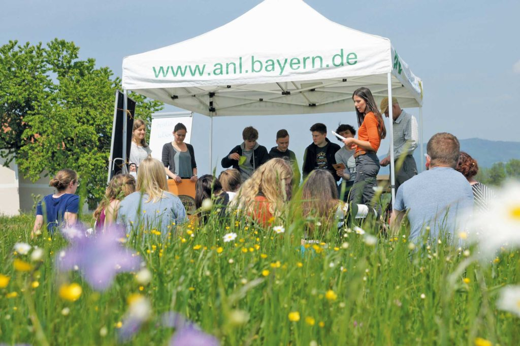Youths sitting in the grass during the first Natura 2000 student event.