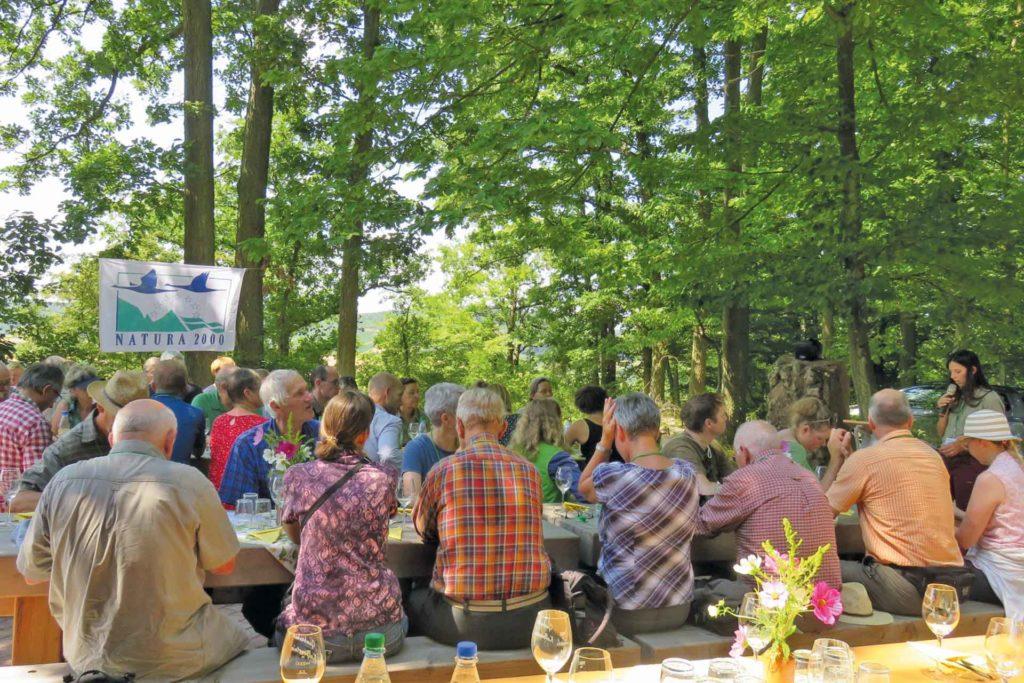 Gruppe von Menschen sitzen zusammen und verkosten Wein. Im Hintergrund weht eine Natura 2000 Fahne. Umgebung: Wald und Natur