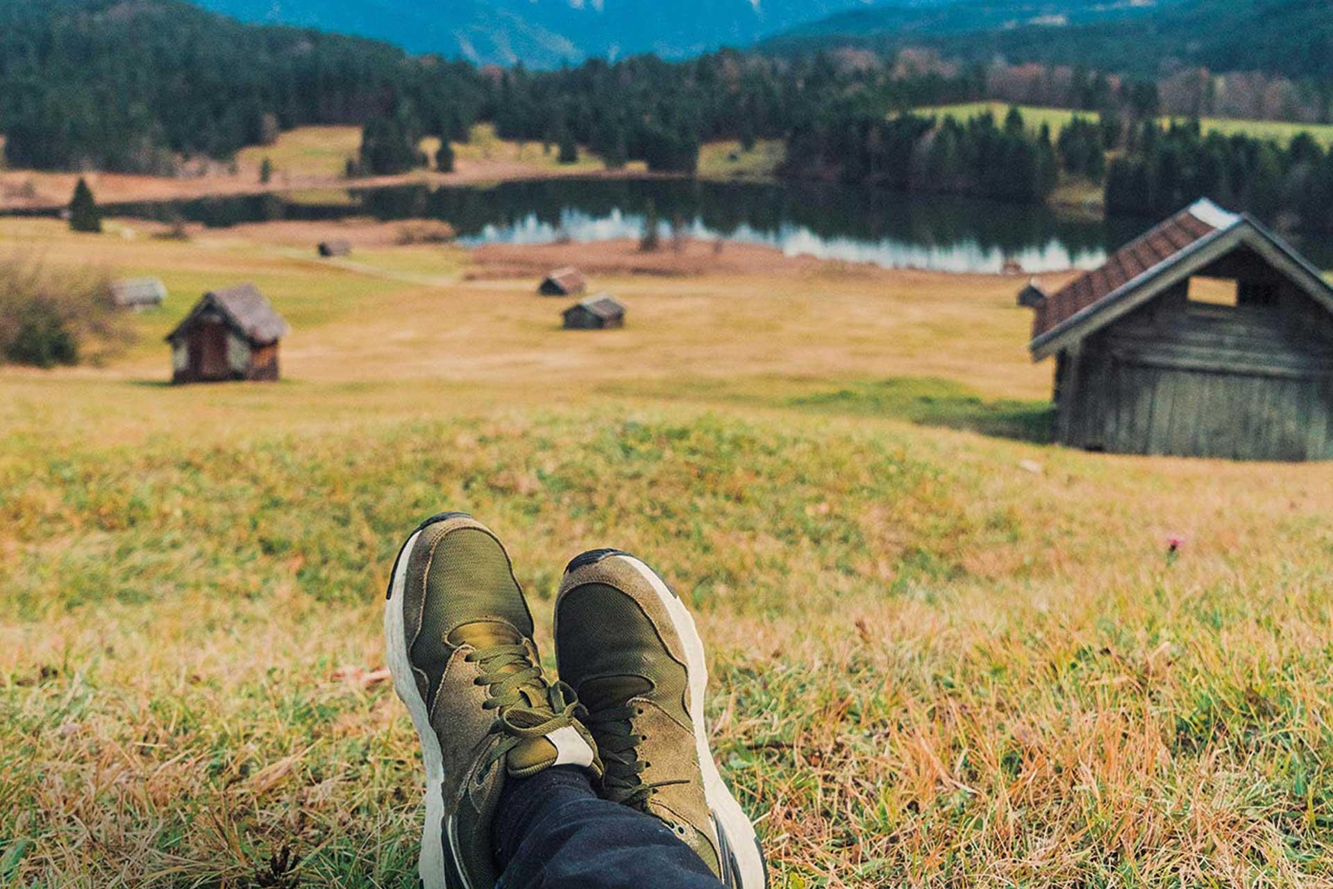 Füße in Olivgrünen Füßen vor dem Hintregrund einer Wiese mit Holzstadeln.