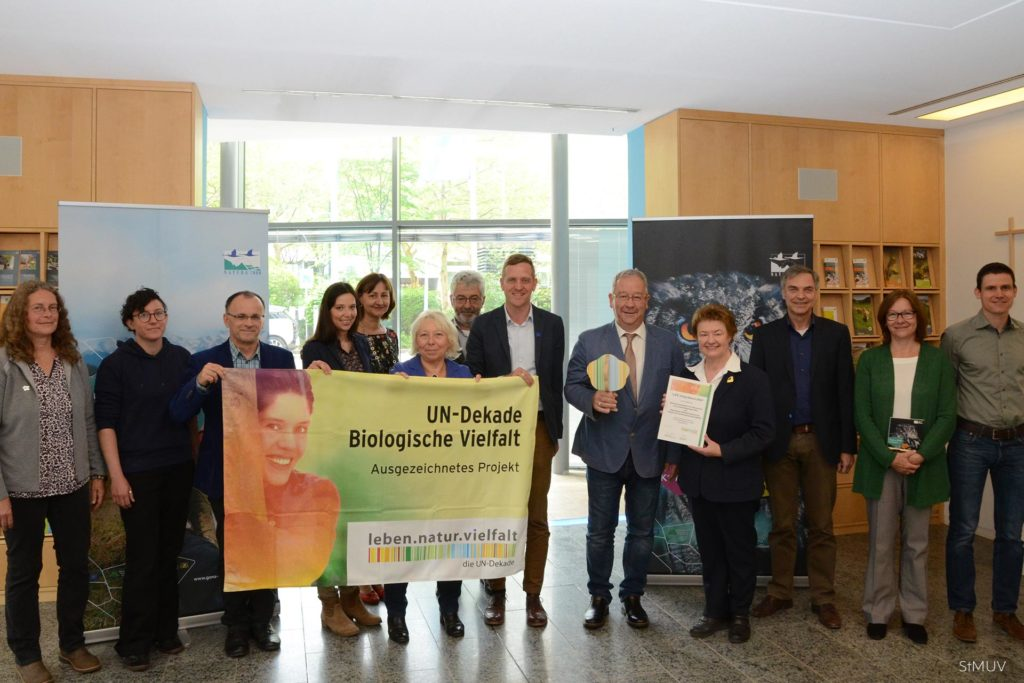 The LIFE living Natura 2000 team receives an award. The team and members of the ministry stand in front of campaign posters while holding a flag showing the award.