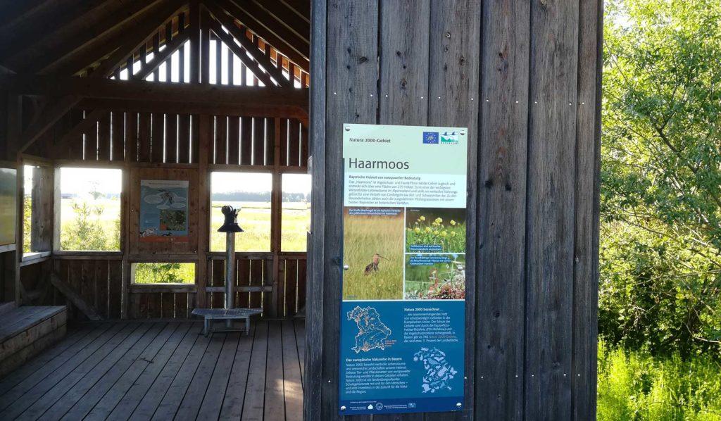 Blick auf eine Hütte im Freien mit Aussichtsglas im Inneren und mehreren Schildern mit Bildern und Texten zum Haarmoos.