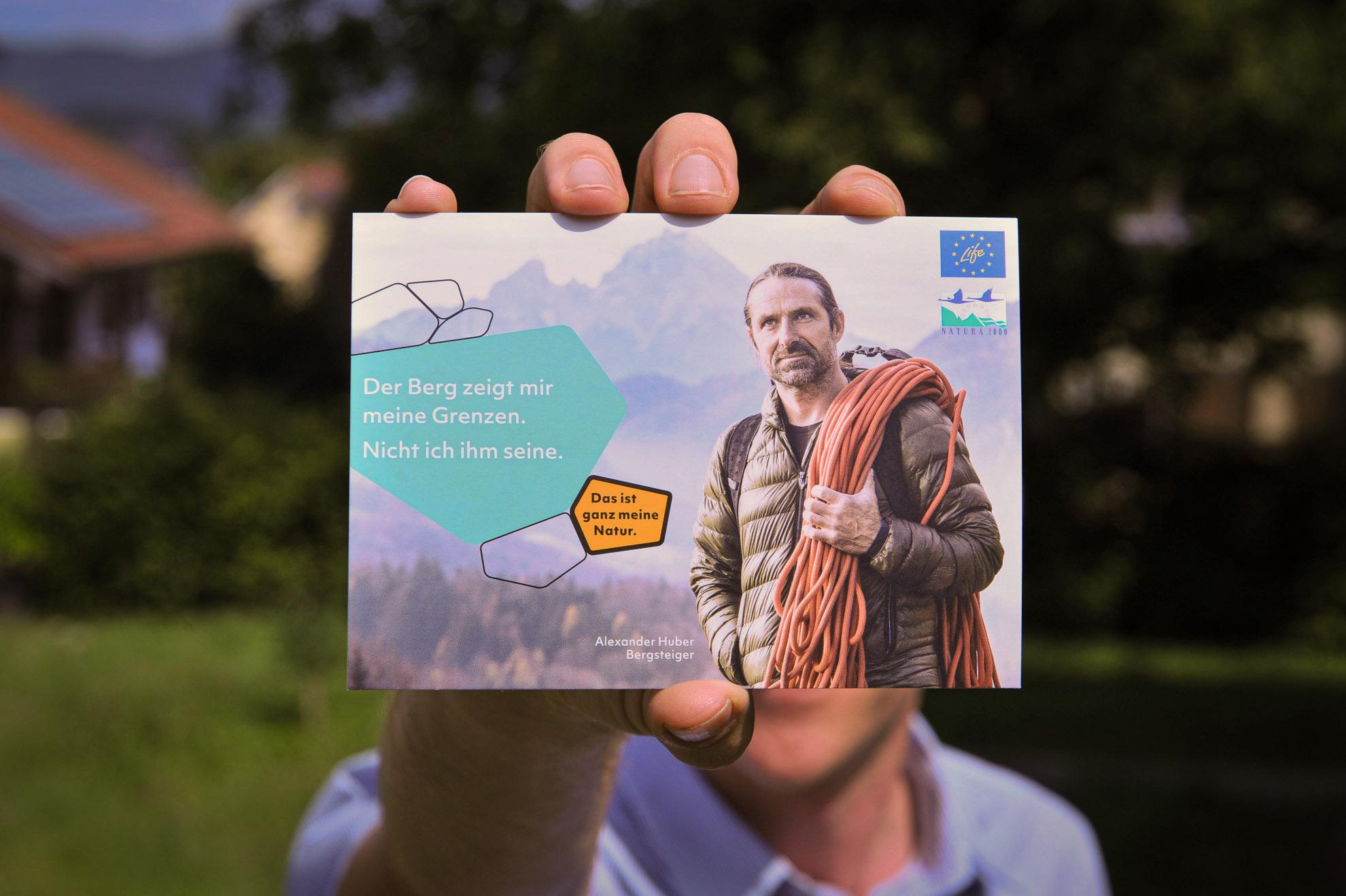 Vorderseite einer Postkarte mit Alexander Huber auf dem Bild, der Bergsteiger und Botschafter von Natura2000 ist, wird von jemandem in die Kamera gehalten.