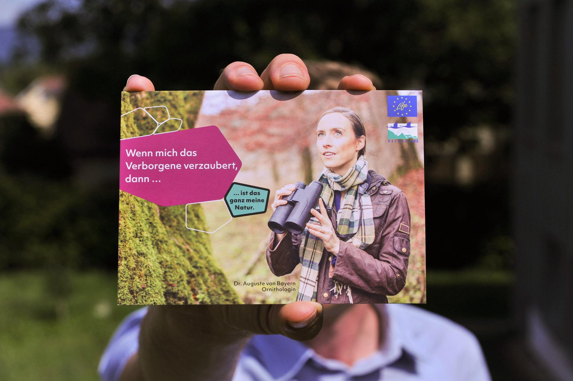 Vorderseite einer Postkarte mit Dr. Auguste von Bayern auf dem Bild, die Ornithologin und Botschafterin von Natura2000 ist, wird von jemandem in die Kamera gehalten.
