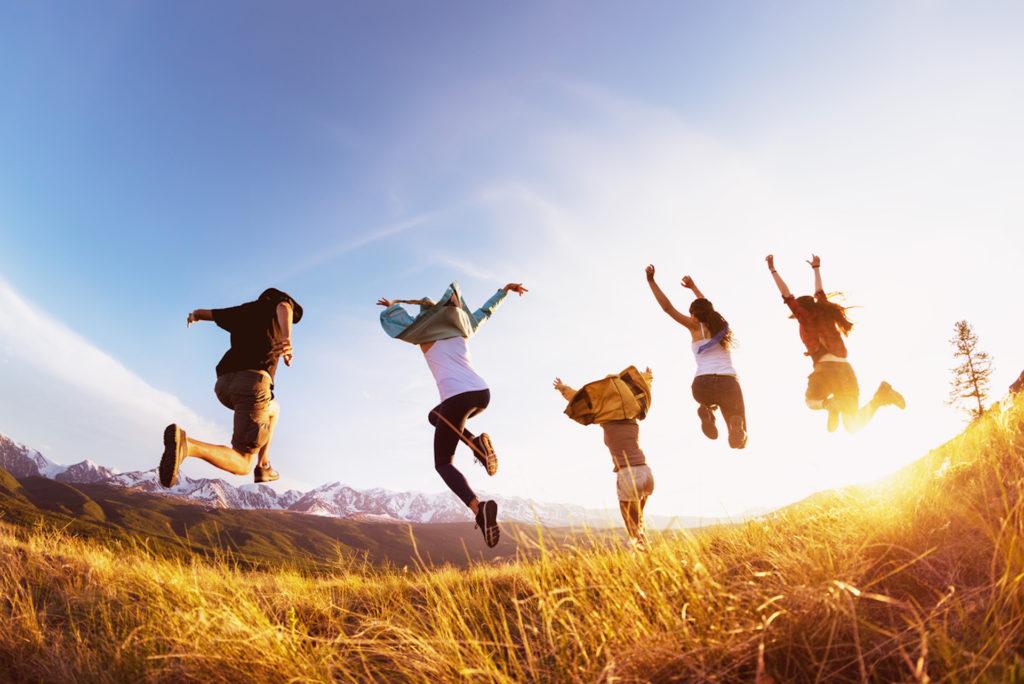 Eine Gruppe an jungen Leuten springt im Sonnenuntergang auf einem Feld in die Höhe
