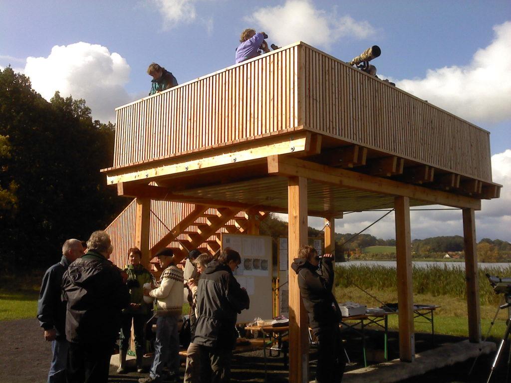 Auf dem Bild steht im Vordergrund eine Gruppe von Personen. Dahinter ist ein eingeschossiger Beobachtungsturm aus Holz zu sehen, von dem aus Personen die umliegenden Vogelvorkommen betrachten.