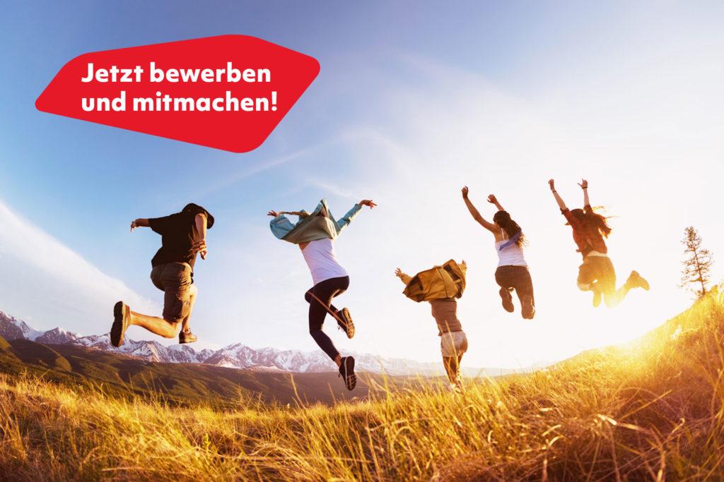 Gruppe junger Leute springt im Sonnenuntergang auf einem Feld in die Höhe. Darüber steht: Jetzt bewerben und mitmachen!