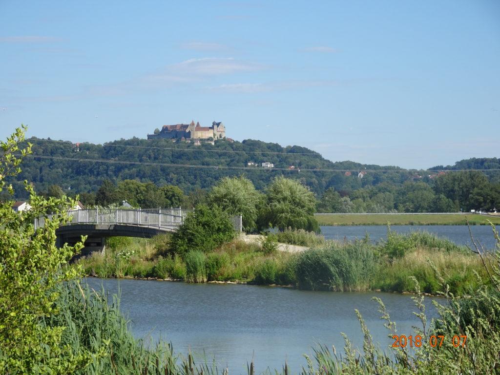 Auf dem Bild befindet sich im Vordergrund ein See, auch ist eine Straße mit einer Brücke zu sehen. Im Hintergrund befindet sich auf einem bewaldeten Hügelrücken eine Burg, die Veste Coburg.
