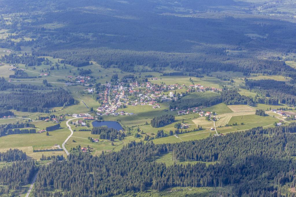 Eine Luftaufnahme der Gemeinde Haidmühle mit dem Dorf Haidmühle im Zentrum. Unmittelbar um das Dorf befinden sich grüne Weiden, Grünland und ein See. An die offenen Bereiche schließen sich weitläufige Fichtenwälder an.