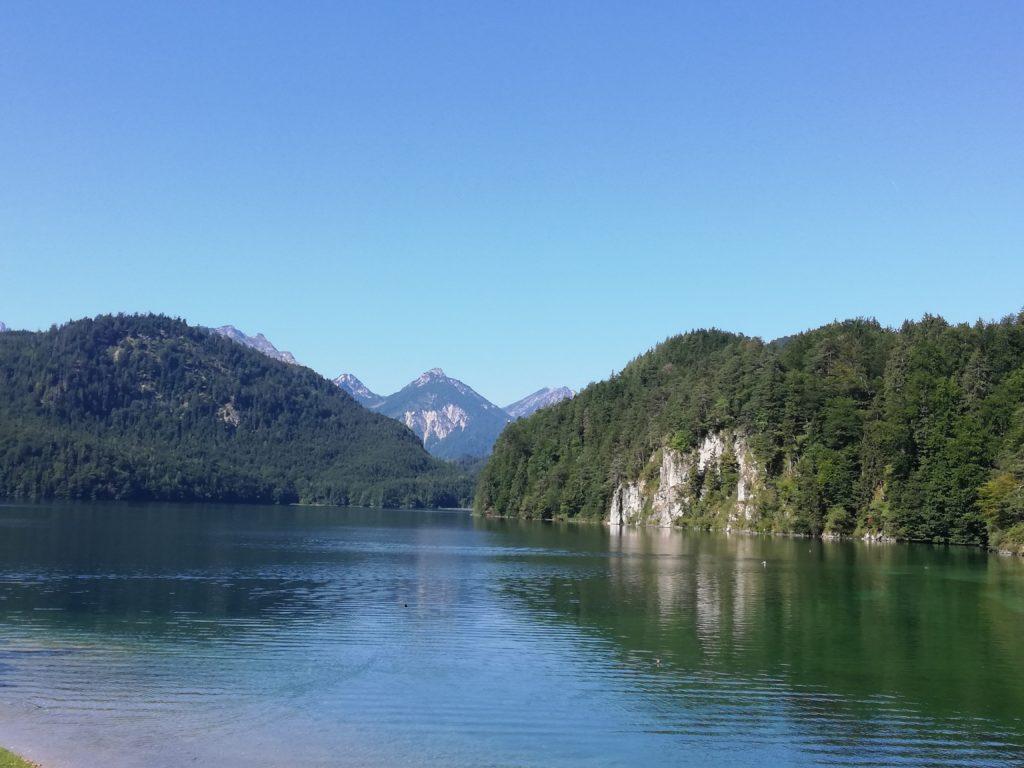 Im Bild ist ein klarer Bergsee zu sehen, umgeben von bewaldeten Berghängen. Im Hintergrund zeichnet sich eine Bergkette ab.