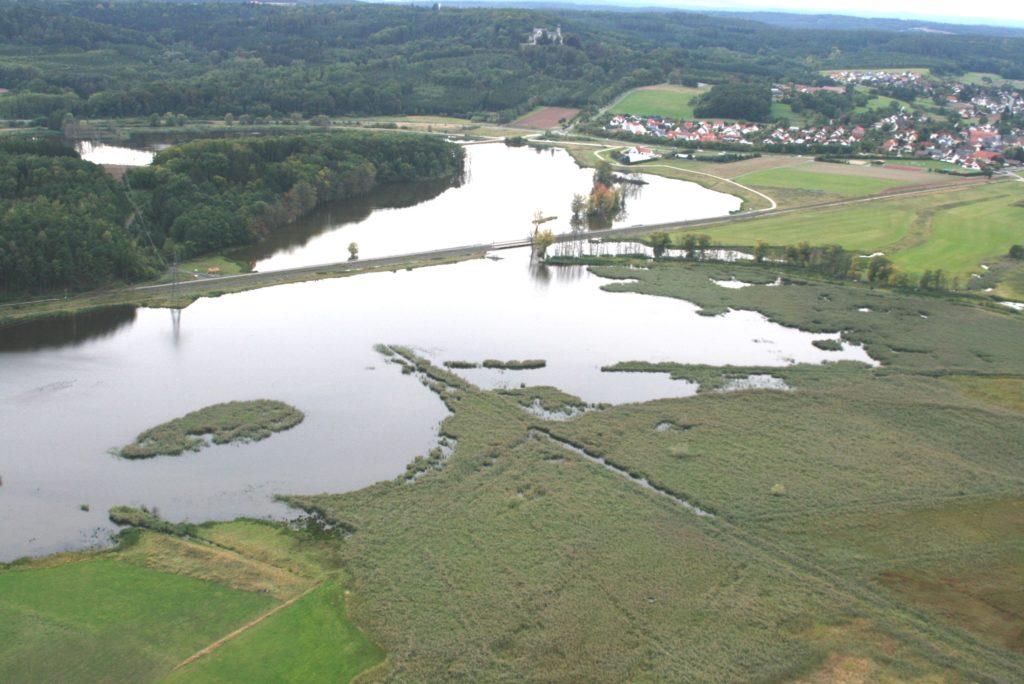 Luftbild einer Landschaft mit überschwemmten Wiesen. Im Hintergrund eine Ortschaft und bewaldete Hänge.