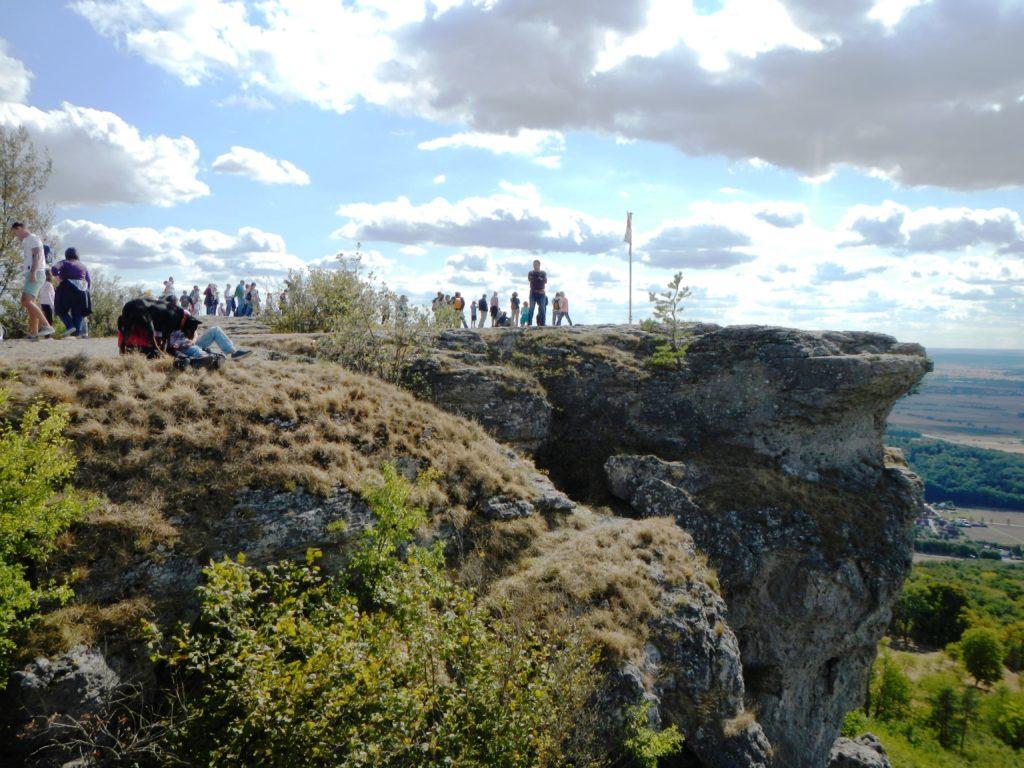 Ein großer Felsen, der Teil des Staffelbergs ist. Auf dem Felsen steht eine Gruppe von Menschen, die die Aussicht in das umgebende Tiefland genießen.