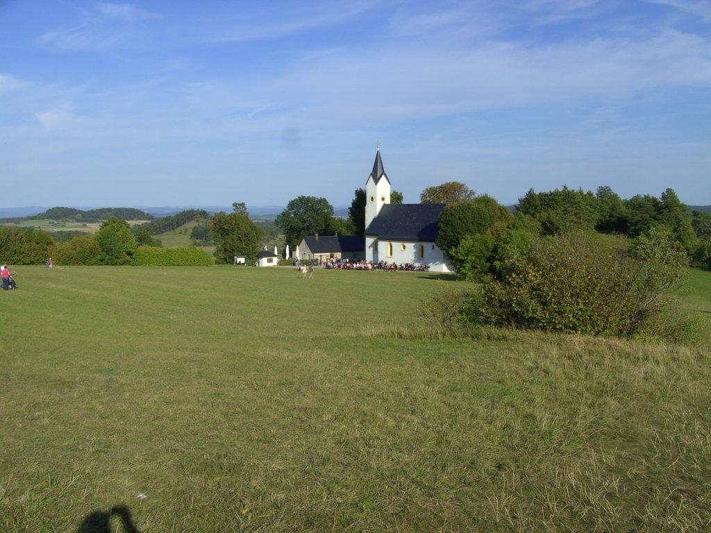 Eine Kapelle, die inmitten einer Wiese liegt und von einigen Bäumen und Büschen umgeben ist.