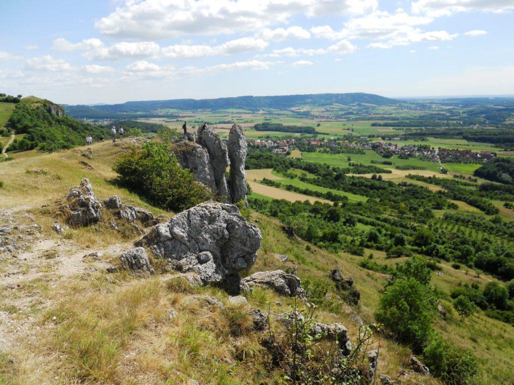 Auf dem Bild sind einige Felsen und ein Hochplateau zu sehen, auf einem Felsen stehen einige Personen und schauen in das darunterliegende Tal.