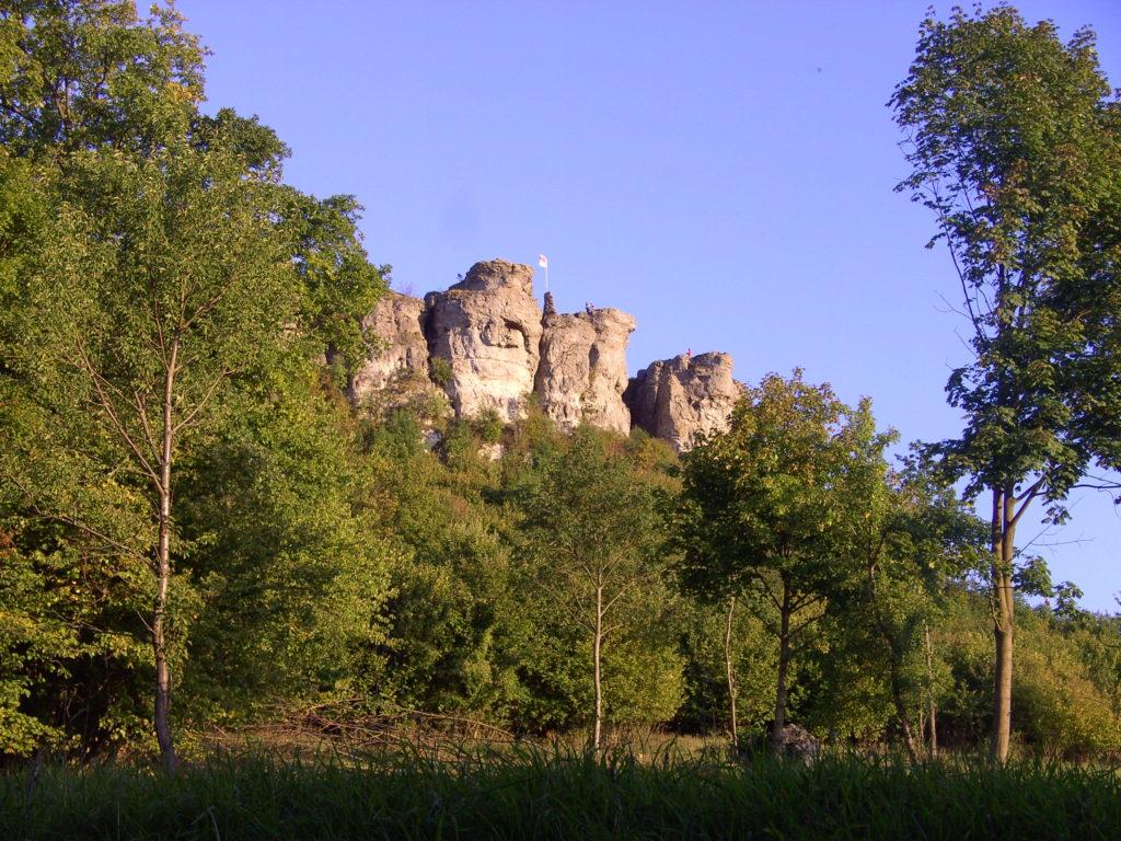 Die markanten Felsen des Staffelbergs. Am Hangfuß schließt sich dicht bewaldetes Gebiet an.