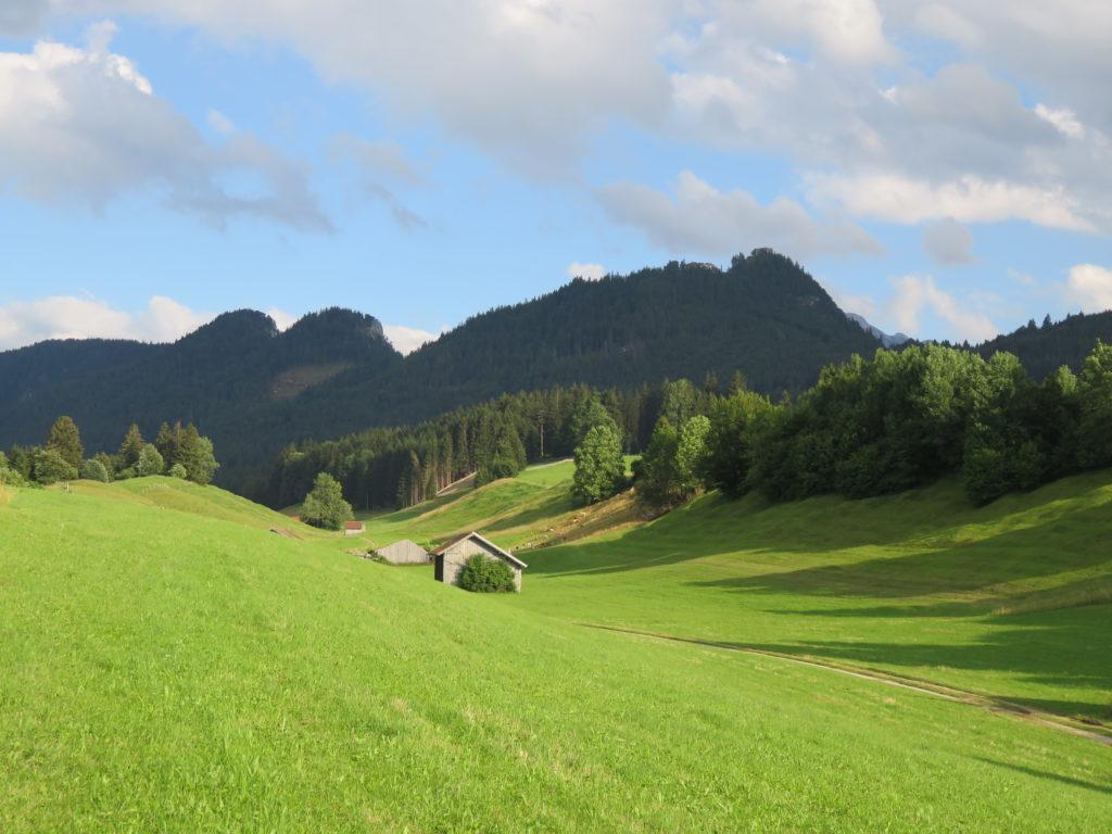 Auf dem Bild ist ein grünes Wiesental mit drei kleinen Scheunen zu sehen, an das Wiesental schließen sich bewaldete Berghänge an.