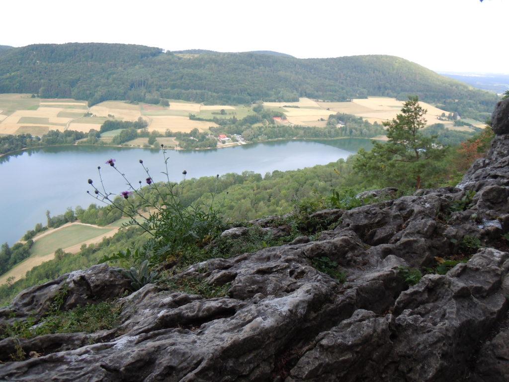 Im Bild ist in der Mitte der Happurger Stausee zu sehen, in der Nähe des Sees befinden sich landwirtschaftliche Flächen, die von bewaldeten Hangkuppen abgelöst werden.