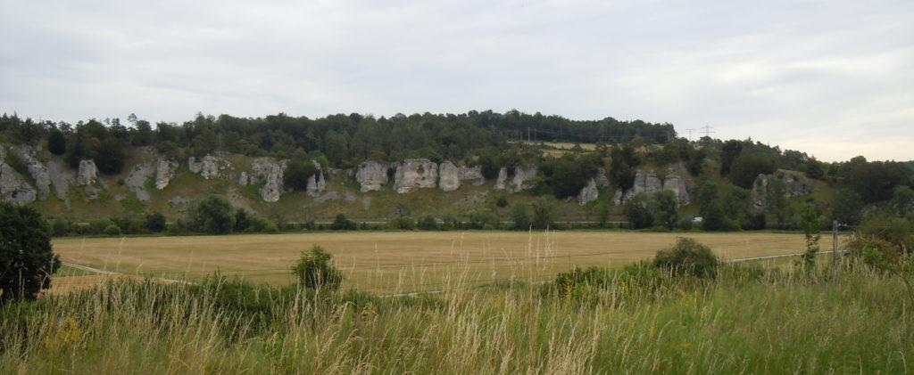 Eine Felsformation, die sogenannten 12 Apostel, davor eine Talebene mit Wiesen und Äckern.