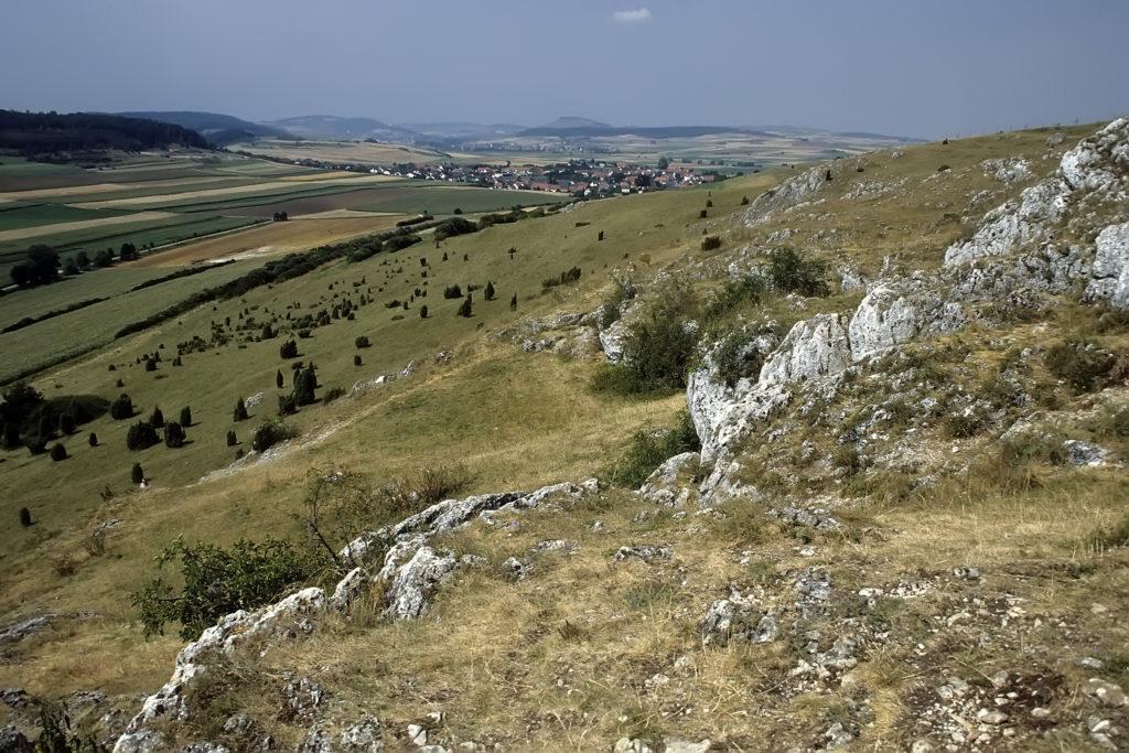 Ausblick vom Berg aus auf das Tal. Andere Berge verschwimmen am Horizont mit dem Himmel, knapp davor ist ein kleines Wohngebiet erkennbar, das sonstige Umfeld besteht aus Feldern. Im Vordergrund ist der Berg relativ felsig und eher kläglich mit Rasen bedeckt.