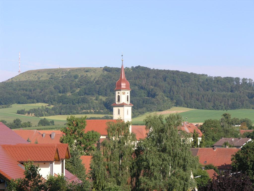 In der Bildmitte ist eine Kirche zu sehen, die Kirche von Röckingen. Im Bildhintergrund ist ein Berg, der Hesselberg, zu sehen. Der Berg ist bewaldet und an einigen Stellen sieht man offene Bereiche, die Kalkmagerrasen.