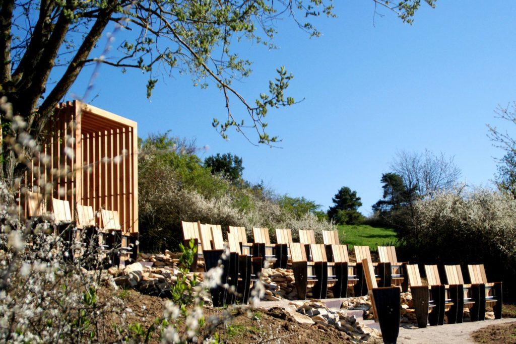 Sicht auf mehrere Reihen Kinostühle aus Holz mitten in der abwechslungsreichen Natur. Hinter den Stühlen ist ein Tunnel aus Holz. Der Himmel im Hintergrund ist strahlend blau.