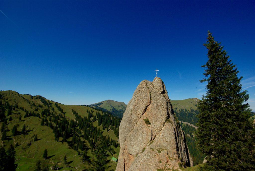 Vor dem Hintergrund der grünen Berge und des blauen Himmels streckt sich kontrastierend ein steiler Fels in die Höhe, auf welchem ein Kreuz steht. Rechts davon ragt ein Nadelbaum ins Bild.