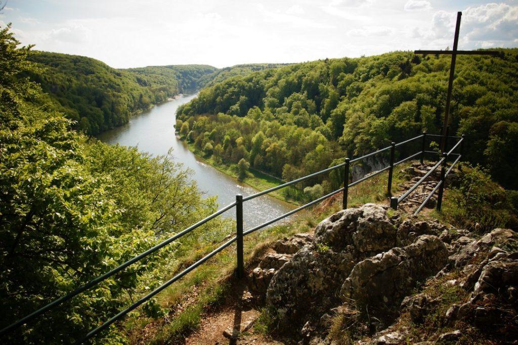 """Das Bild ist dem Aussichtspunkt """"Wieser Kreuz"""" oberhalb der Donau aufgenommen. Über eine Geländer auf einer Felskuppe ist die Donau inmitten von Wäldern zu sehen."""