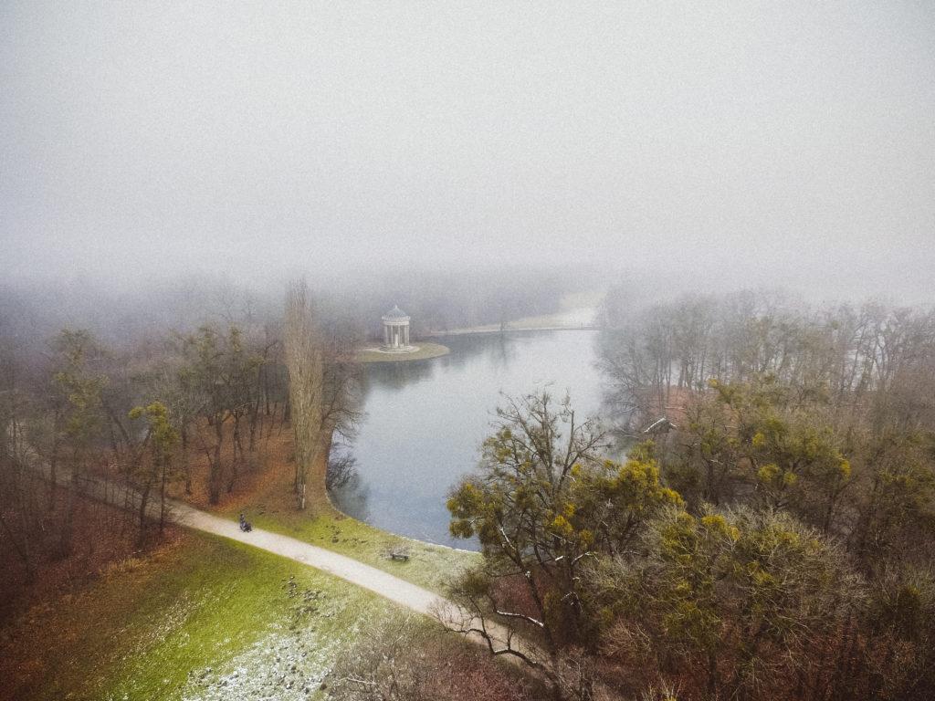 Ein Park mit Wasserfläche und Bäumen im winterlichen Nebel. Ein Pavillon steht am Uferrand der Wasserfläche und eine Person geht mit einem Kinderwagen entlang eines Weges spazieren.