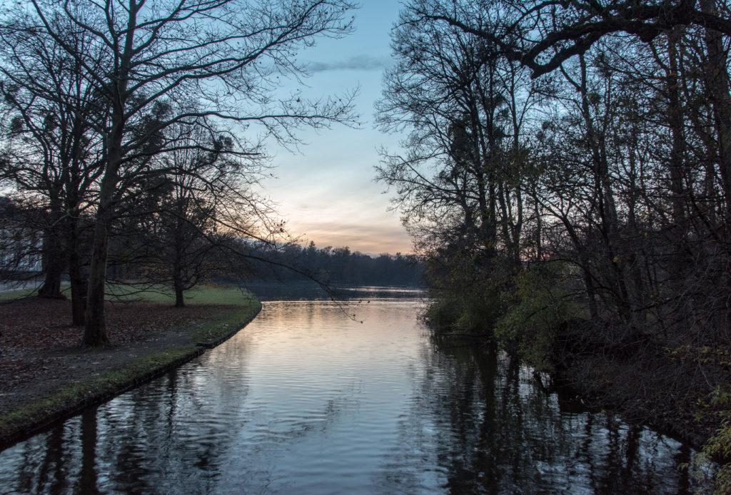 Ein Wasserkanal inmitten von Parkflächen mit Wiese und Bäumen. Auf dem Wasser spiegelt sich das letzte Abendlicht eines Wintertages.