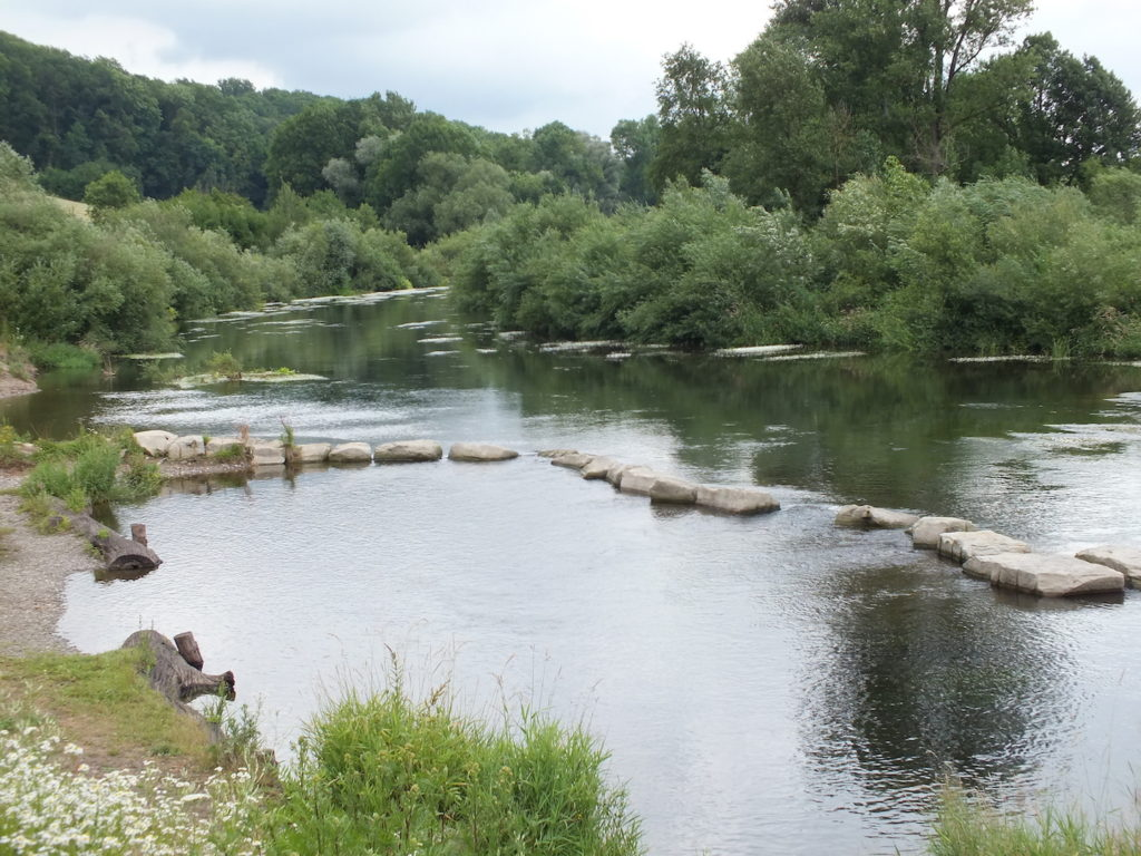 Ein Fluss, im Flussbett grenzen größere Steine im Wasser eine Badestelle ab.