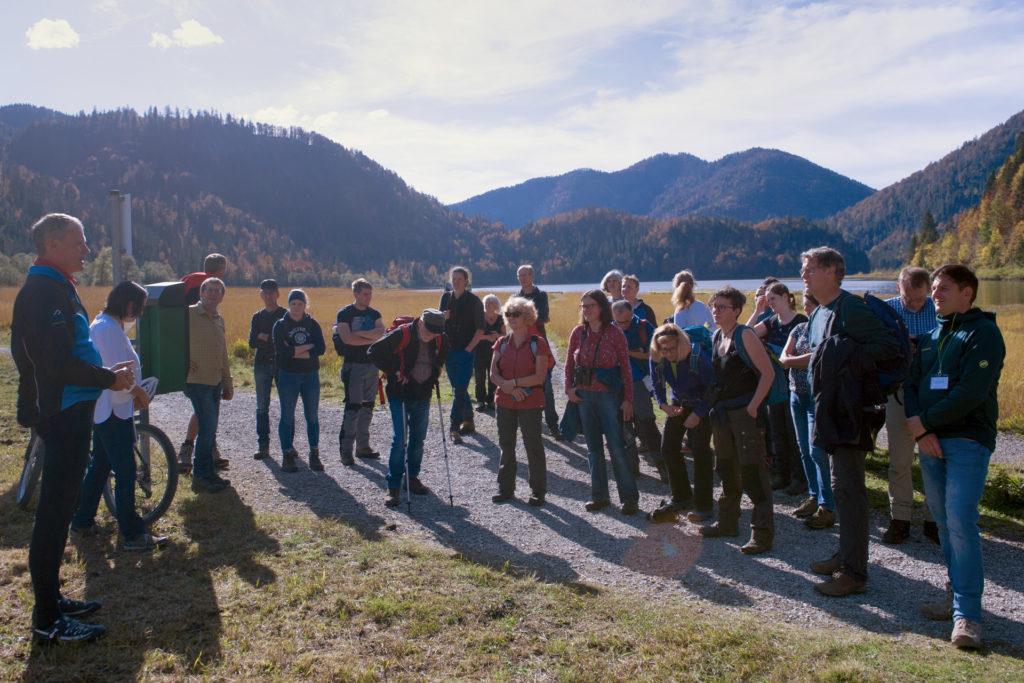 Exkursionsgruppe mit circa 25 Teilnehmern, im Hintergrund der Weitsee und Berge.