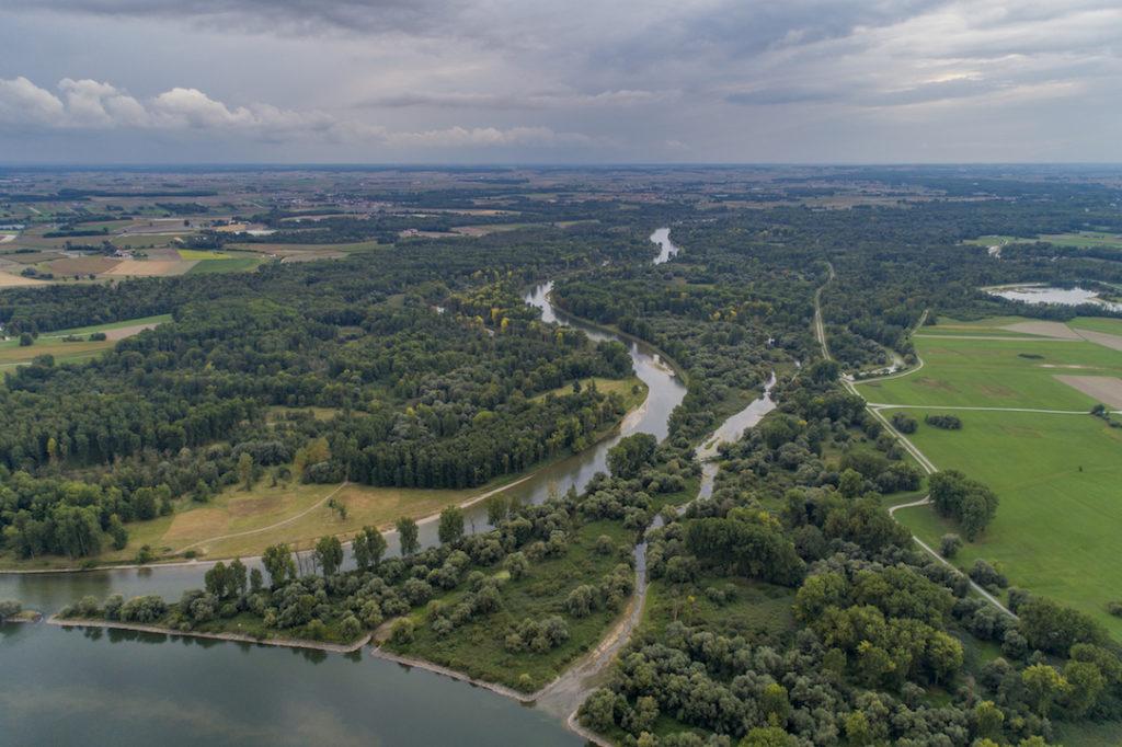Das Bild zeigt eine Luftaufnahme der Isarmündung. Die Isar fließt von der Mitte der oberen Bildkante durch das Bild und mündet in der linken unteren Bildecke in die Donau. Die Flussufer sind bewaldet. Weiter entfernt finden sich Grünlandbereiche und Äcker in einer sommerlichen Landschaft unter regenschwerem Himmel.