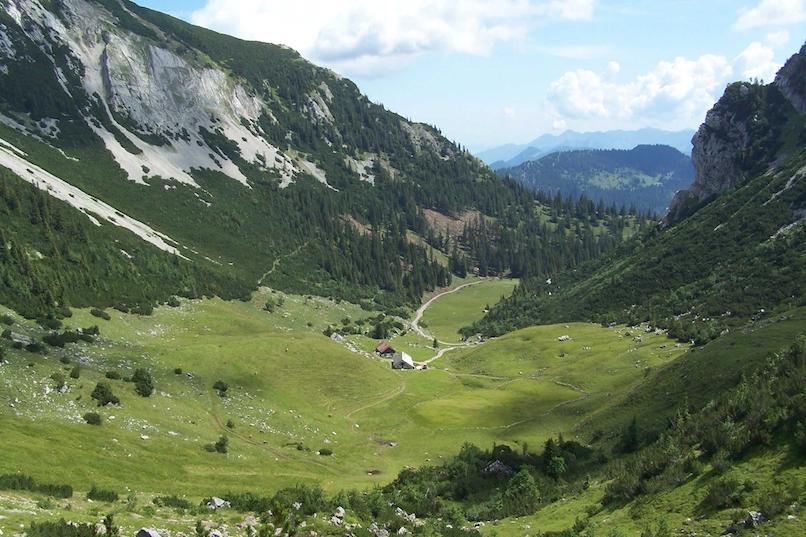 Der Bild zeigt ein Tal mit einer Almfläche und Almgebäuden. Zu beiden Seiten ragen Berge mit Felswände bewaldeten Hängen auf. Über das Tal blickt man hinaus auf Bergpanorama in der Ferne.