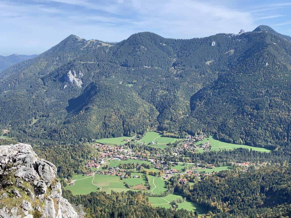 Das Foto zeigt eine bewaldete Bergkette. Am Fuß der Berge befindet sich eine Ortschaft zwischen Bäumen und grünen Wiesen.