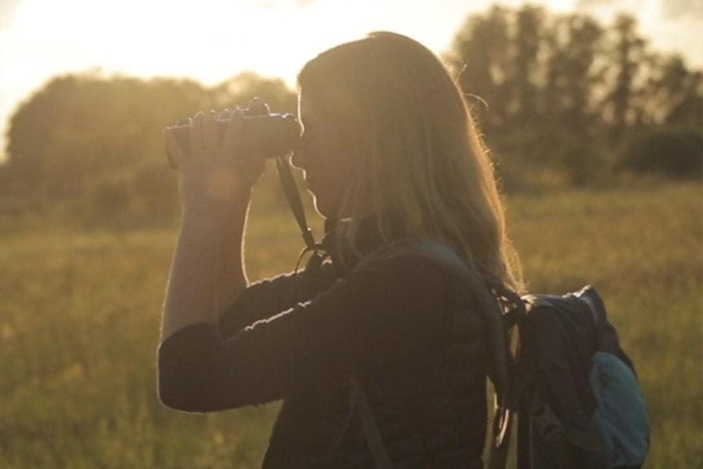 Eine Frau steht im Gegenlicht auf einer Wiese und sieht durch ein Fernglas.