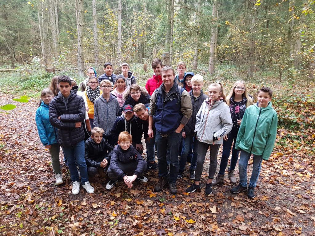 Eine Schulklasse mit Lehrer steht in einem herbstlichen Wald.