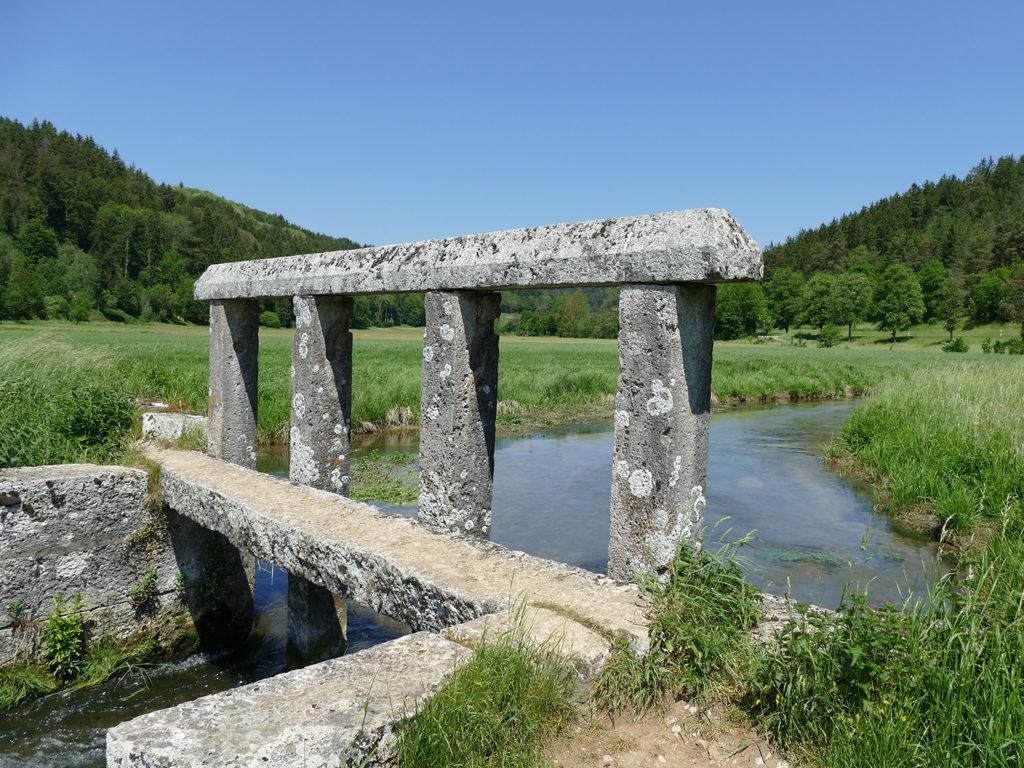 Steinbrücke, die über einen Fluss führt, welcher durch Wiese läuft.