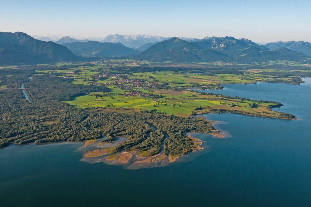 Landschaftsbild mit Bergen, Grünflächen und Wasser