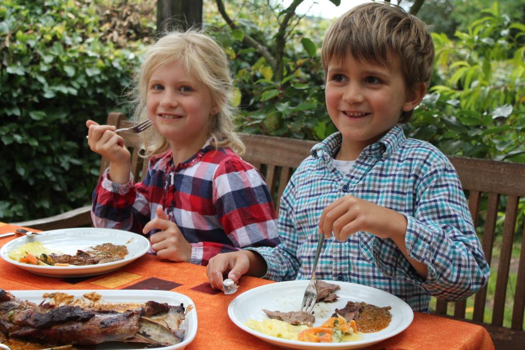 Zwei lächelnde Kinder beim Essen