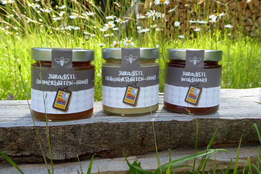 Drei Honiggläser mit verschiedenen Honigsorten