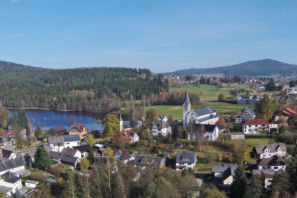 Dorf umgeben von Natur und einem See