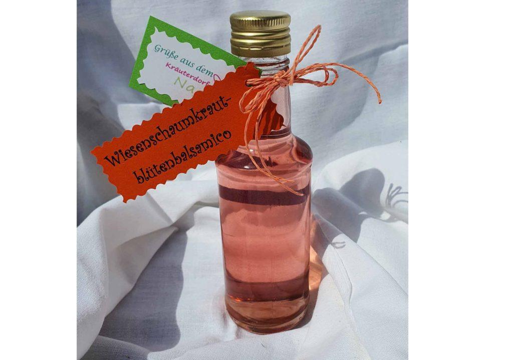 Rosafarbener Essig in einer Glasflasche mit einem roten Etikett.