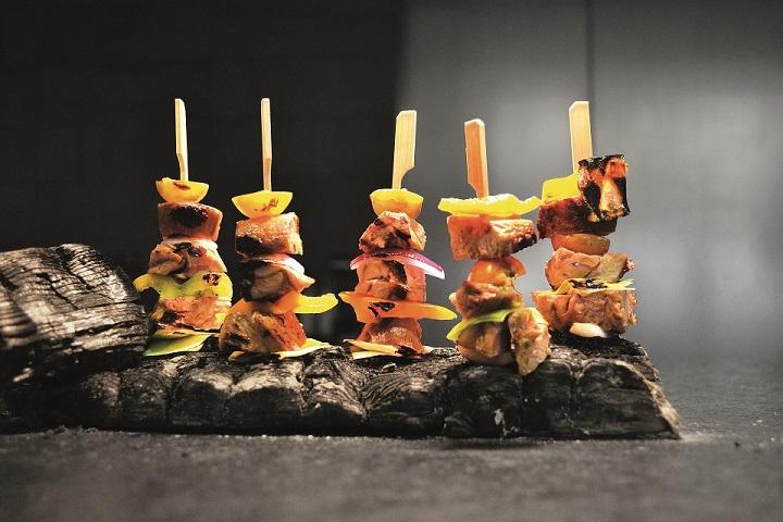 Spieße mit Lammfleisch und Gemüse auf einer Platte angerichtet.