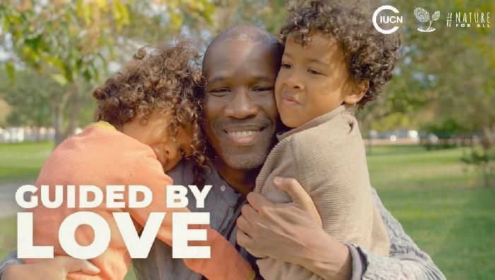 Ein Vater hält seine beiden Töchter im Arm, im Vordergrund die Aufschrift Guided by Love.